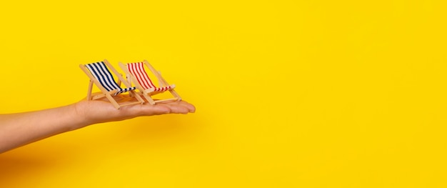 手持ちのサンベッド、夏休み、黄色の背景のパノラマレイアウト