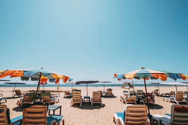 Лежаки на тропическом пляже с спокойным небом. вид на море и песчаный пляж, летний фон.