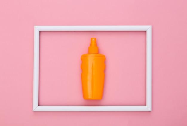 핑크 화이트 프레임에 자외선 차단제 병입니다. 피부 보호. 해변 휴가