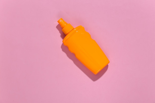 Sunblock bottle on pink bright sunny. skin protection. beach vacation.
