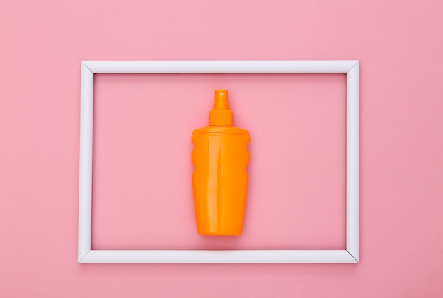 Sunblock bottle on pink with white frame. skin protection. beach vacation