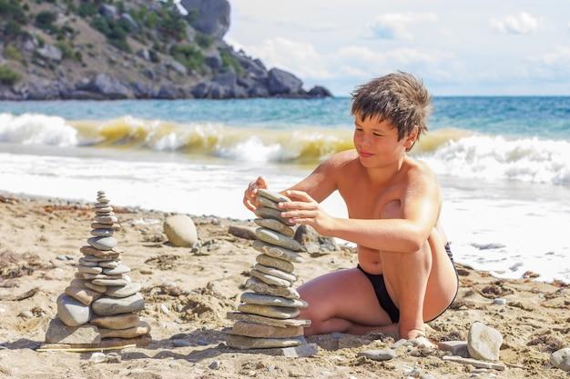 Загорелый мальчик играет с галькой на пляже