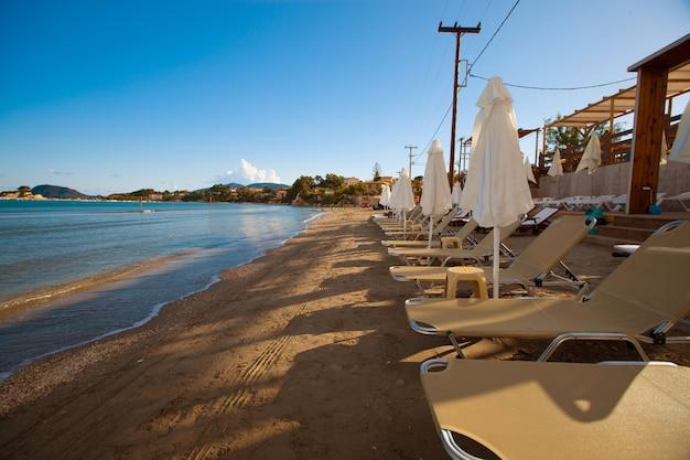 Sunchairs с зонтиками на прекрасном пляже
