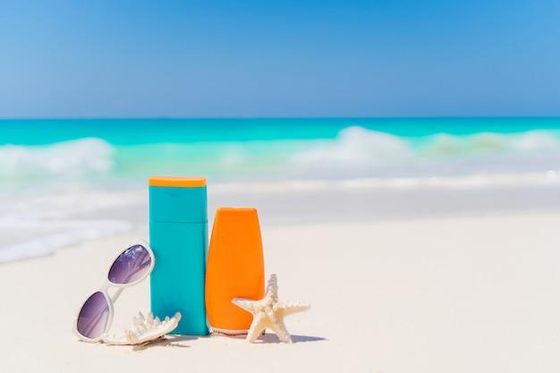 Suncream bottles, sunglasses, starfish on white sand background ocean