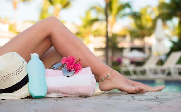 Suncream, шляпа, солнцезащитные очки, цветочные и загорелые женские ножки возле бассейна