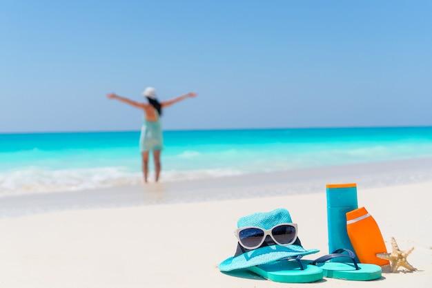 Suncreamボトル、サングラス、白い砂の上のフリップフロップ