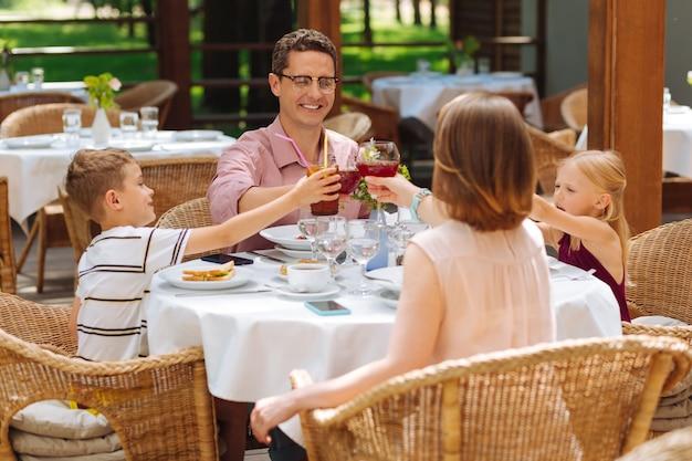 일요일 아침. 레스토랑의 여름 테라스에서 전통적인 일요일 아침 식사를하는 행복한 가족