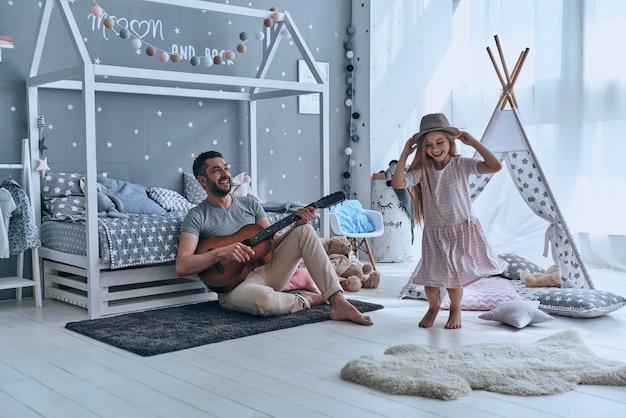 日曜日の楽しみ。幼い娘のためにギターを弾いて笑っている若い父親