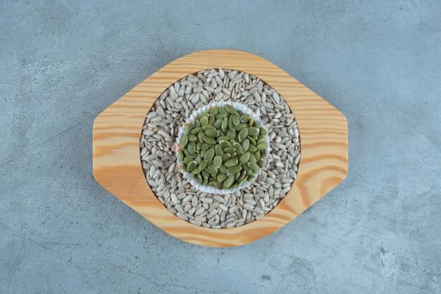 Семечки подсолнечника и зеленые тыквы на деревянном блюде. фото высокого качества