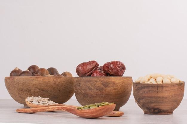 ひまわりとカボチャの種と白い表面のナッツのボウル。