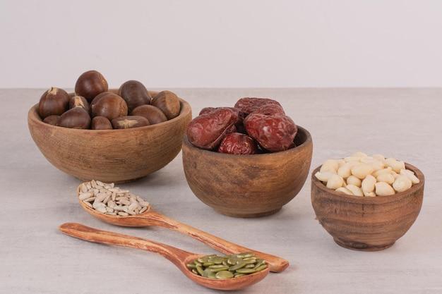 Семена подсолнечника и тыквы и миски орехов на белой поверхности.