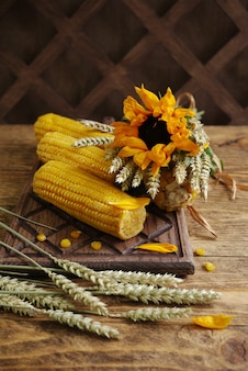 Sunflower flower and ears of boiled corn on a wooden chopping board country style selective focus