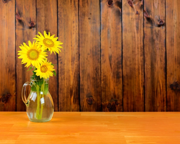 Sunflower flowers in a vase on the table. brown wooden planks background.
