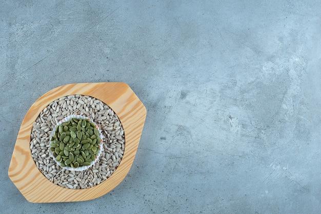 Semi di girasole e zucca verde su un piatto di legno. foto di alta qualità