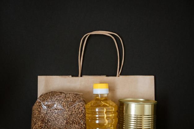 黒の背景、寄付の概念のパッケージとひまわり油のシリアル