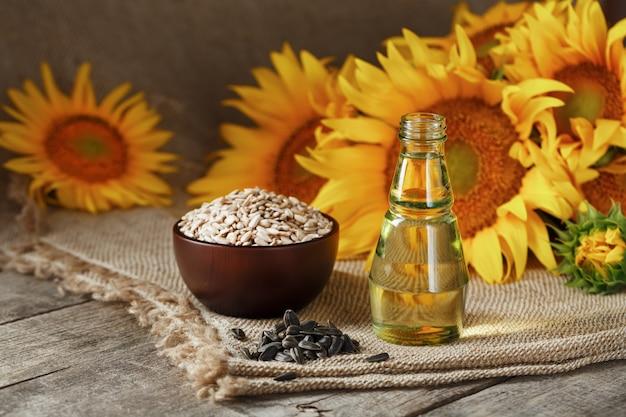 Подсолнечное масло в стеклянной бутылке с семенами в чашке и цветами на деревянном столе.