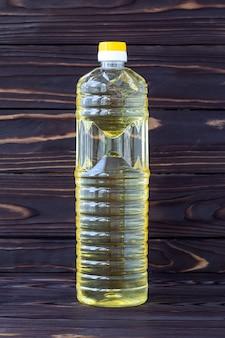 暗い木の板のペットボトルのひまわり油、黄色のサラダ油、透明なパッケージ。健康的なオーガニック製品。食品成分、植物性脂肪。