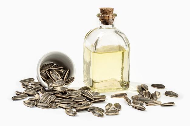 ガラス瓶のひまわり油と白で分離された種子