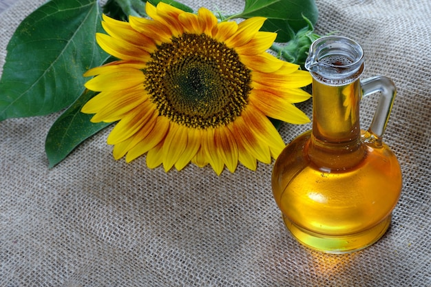 Sunflower oil and a sunflower flower on the table. natural vegetable oil.