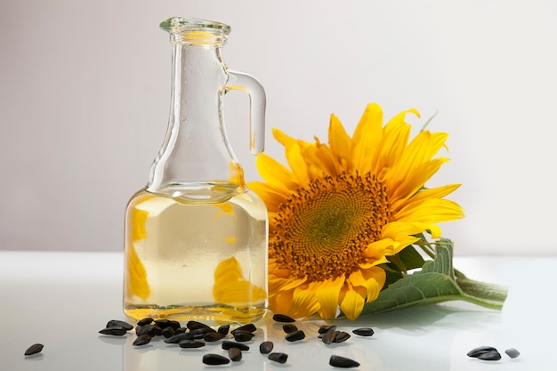 Sunflower oil in a transparent jug with sunflower flower