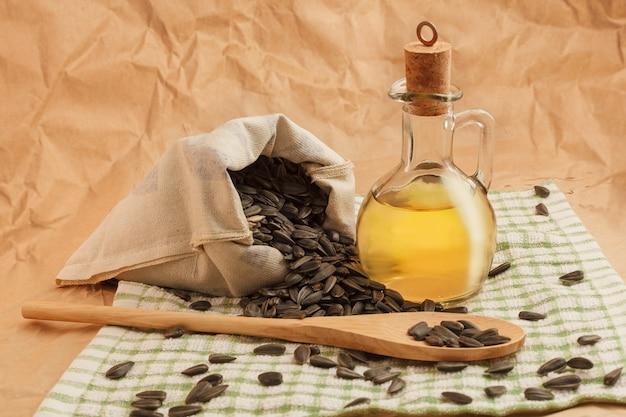 씨앗 한 봉지와 나무 숟가락이 든 해바라기 기름