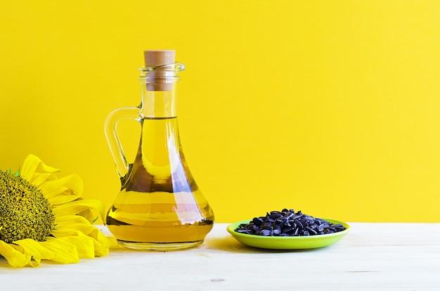 Подсолнечное масло с цветком и семенами в стеклянном кувшине.