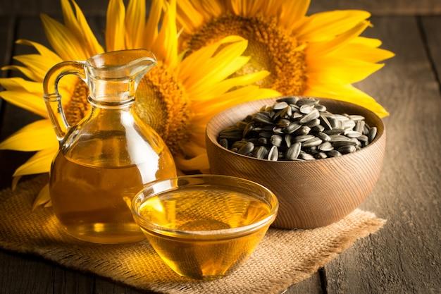 Подсолнечное масло с семенами на деревянных фоне.