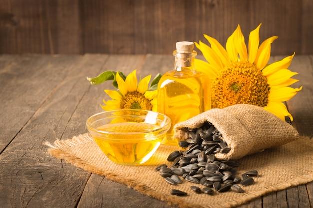 Подсолнечное масло с семенами на деревянном фоне