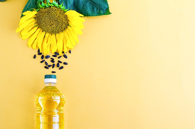 Подсолнечное масло с желтым цветком и семенами в бутылке.