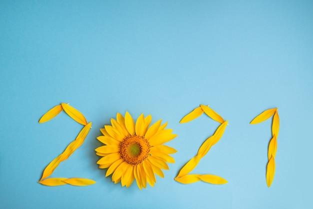Лепестки подсолнуха в виде цифр 2021 на синем фоне. 2021 год, новый год, новая реальность. лето пора путешествовать
