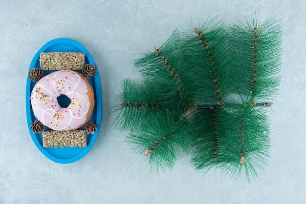 ひまわりの種のスナックバーと、大理石の人工松の枝の横にある大皿に松ぼっくりのドーナツ。