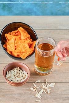 Семечки, миска чипсов и стакан пива на деревянном столе.