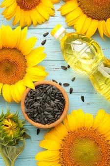 Семена подсолнечника и бутылка масла на синем деревянном столе. вертикальное фото