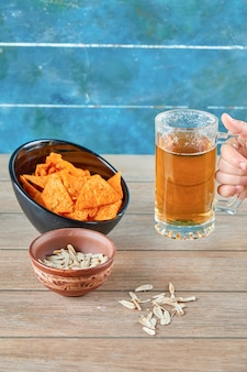 Sunflower seeds, a bowl of chips and a glass of beer on wooden table.