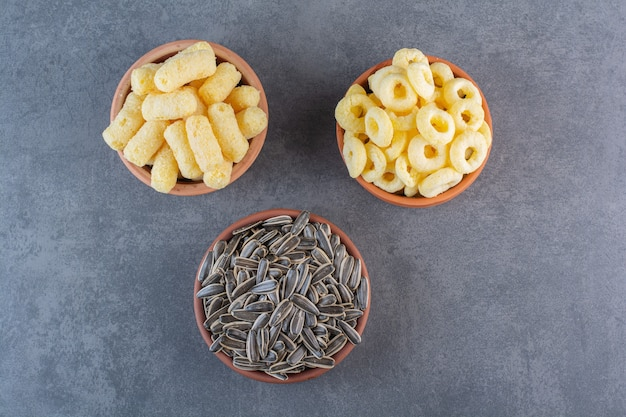 대리석 표면에 있는 그릇에 해바라기 씨, 옥수수 스틱, 옥수수 링