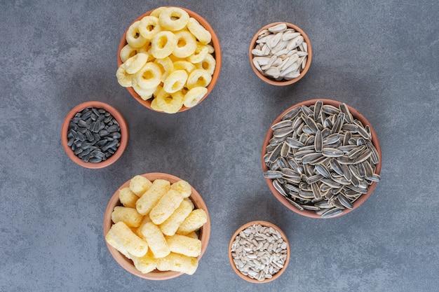 Семена подсолнечника, кукурузные палочки и кукурузное кольцо на мисках, на мраморной поверхности