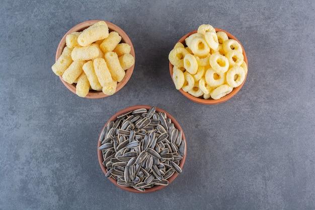 Semi di girasole, bastoncini di mais e anello di mais su ciotole, sulla superficie di marmo
