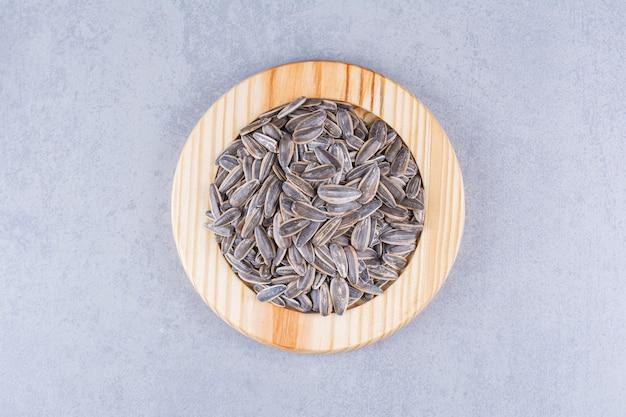 Семечки в деревянной тарелке на мраморе.