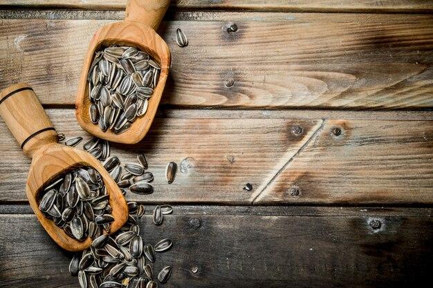 木製のテーブルのスクープのヒマワリの種。