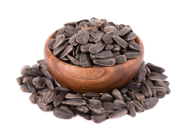 절연 해바라기 씨앗입니다. 나무 그릇에 튀긴 된 해바라기 씨의 더미입니다.