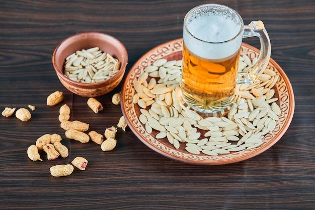 木製のテーブルにひまわりの種、ピーナッツ、ビールのグラス。