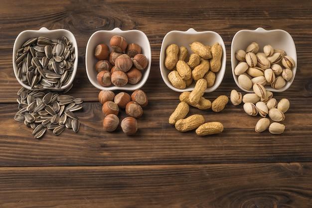 해바라기 씨, 땅콩, 헤이즐넛, 피스타치오가 나무 테이블 위의 컵에서 흘러 나옵니다. 견과류와 씨앗의 혼합물.