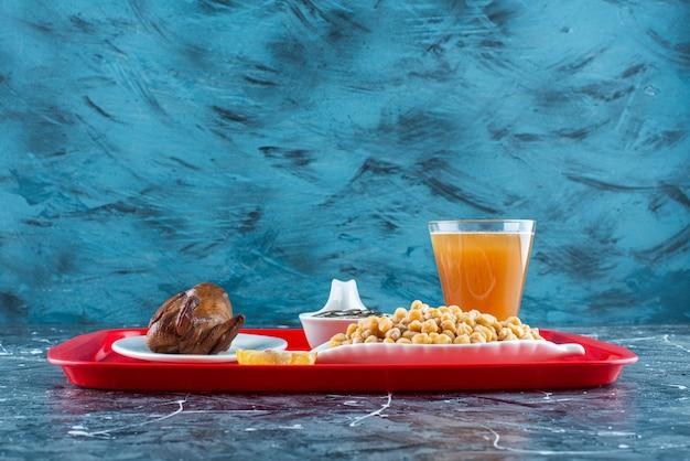 ひまわりの種は、大理石のテーブルのトレイにレモン、グリルチキン、ビールをスライスしました。