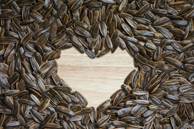Текстура семян подсолнечника делает форму сердца на среднем фоне