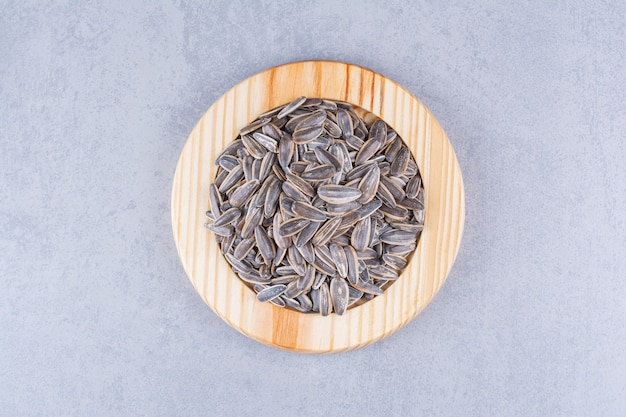 Sunflower seeds in a wooden plate on marble.