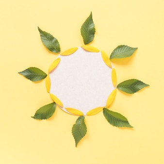 Sunflower shaped decoration made up of leaves; petals and blank cardboard paper