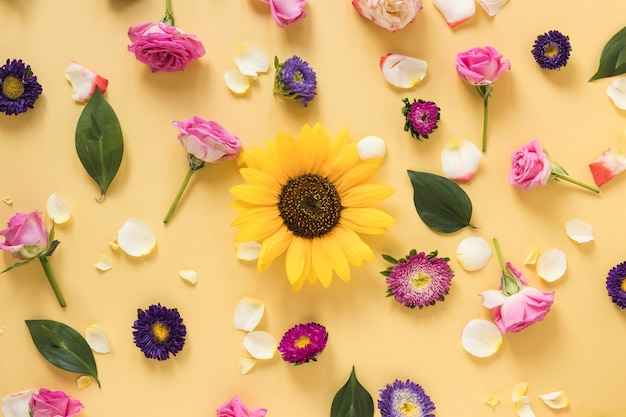 Sunflower surrounded with different types of flowers on yellow background