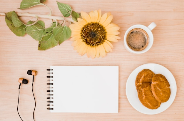 Sunflower twig; coffee cup; earphone; cookies and blank spiral notepad on wooden desk