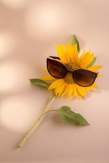 베이지색 종이 배경에 선글라스를 끼고 있는 해바라기는 미니멀하고 트렌디한 정물