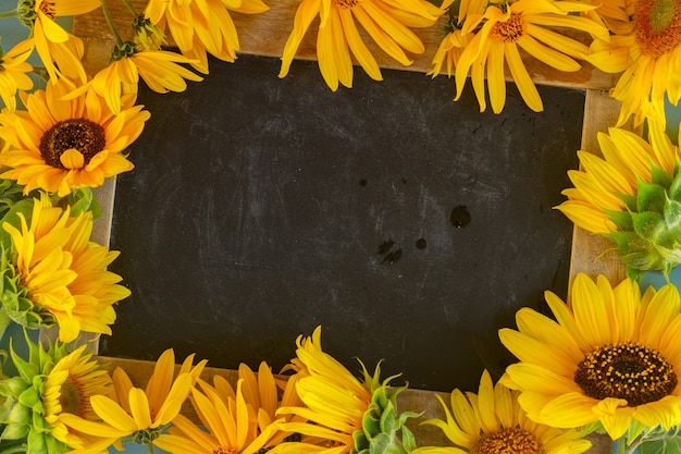 Sunflowers on blue wooden background, copy space on blackboard, top view